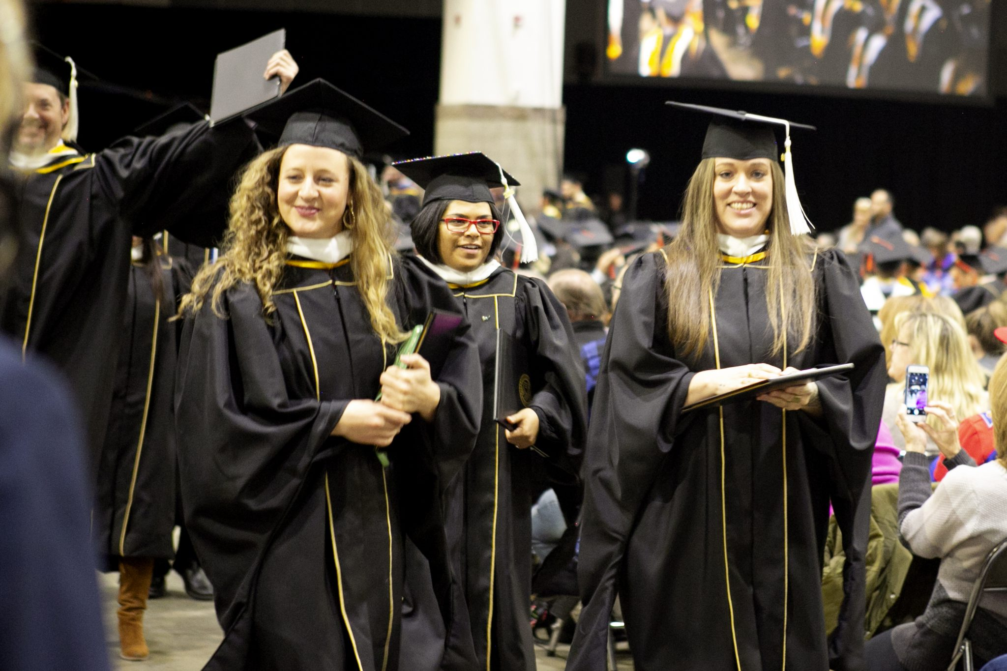SEHD grads walking down isle after receiving diploma during fall commencement 2018