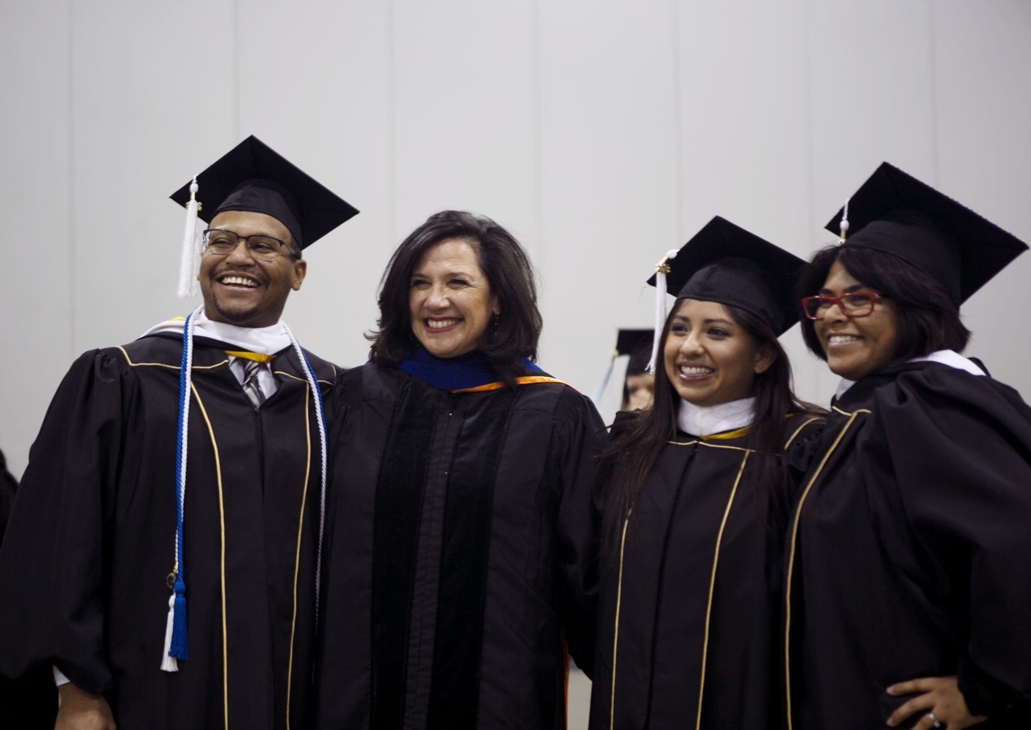three students with their professor wearing grad regalia at fall commencement